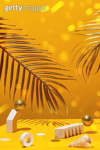 Golden candles with the new year 2021 on the marble arch, palm leaves, column, stairs, balls, Christmas trees, confetti on a yellow background with the horizon. Festive trend still life