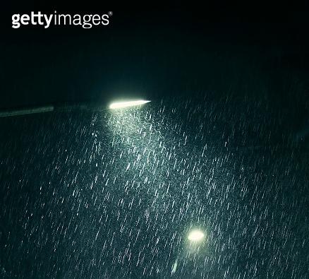 Raindrops illuminated in streetlight at night