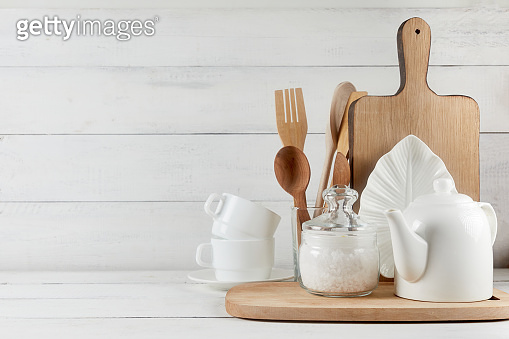Kitchen wide banner concept. Kitchen background for mockup with spoon, teapot, cups, bowls, flowers on wooden table .