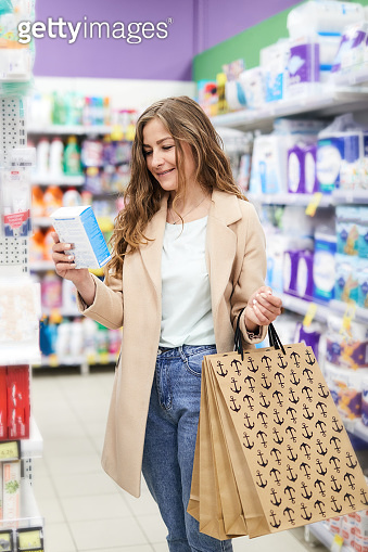 Young woman shopping at the supermarket and reading information on a box. Economical and useful purchases.