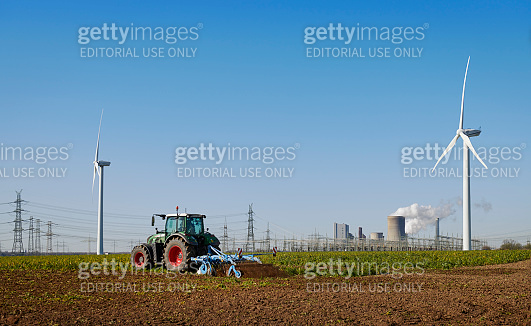 Green tractor and wind turbines in front of a power plant