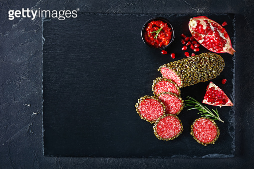 salami coated with whole green peppercorns and have sliced on a black stone board