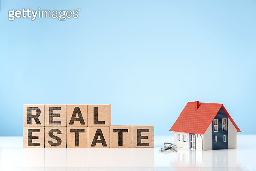 REAL ESTATE word on wooden cube with Model house and house key. Business concept