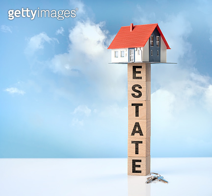 A dreamlike house among the clouds and ESTATE word on wooden cubes. Business concept