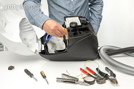 Repairman repairing of vacuum cleaner