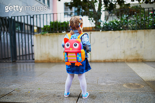 Adorable toddler girl with funny backpack ready to go to daycare, kindergarten or school