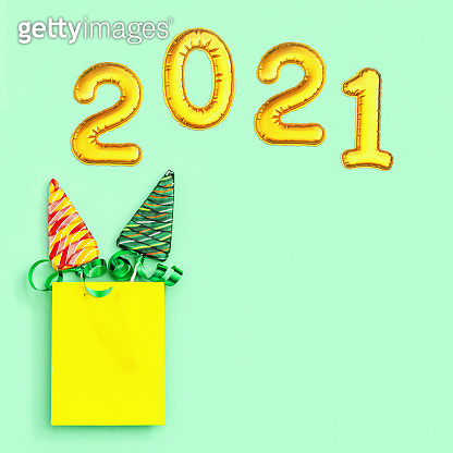 Color candy creative for New Year or Christmas. Lollipops shaped like Christmas tree and metallic golden inflatable figure 2021 on neo mint colored paper background. Top view.