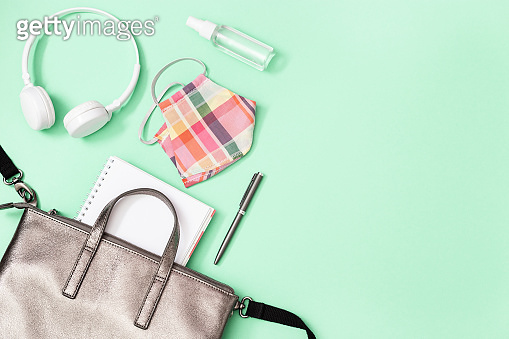 Grey leather backpack with school supplies and Personal protective equipments.  Face Shields and hand sanitizer, copybooks, pens. Back to school concept. Close up, copy space, flat lay.