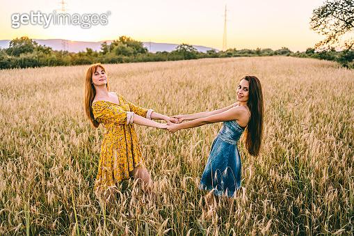 Young women having fun in wheat field