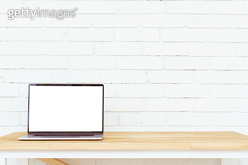 Laptop with white blank screen on wooden table. Open space.