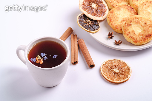 Cottage cheese fritters with hot black aromatic tea, Christmas breakfast mood with anise and cinnamon on white background, angle view