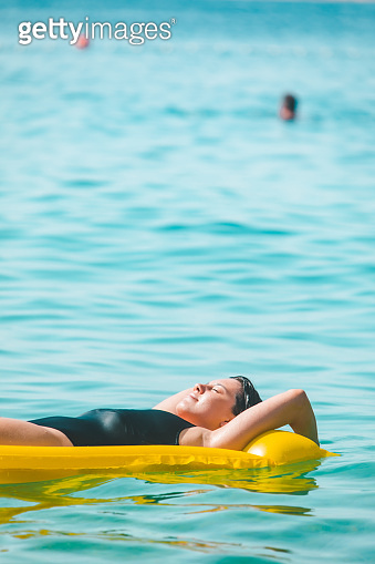 beautiful sexy woman laying on yellow inflatable mattress at sea water