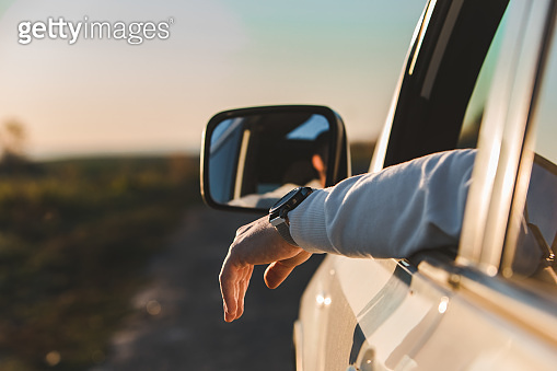 man stick out hand from car window. relaxed enjoying at sunset
