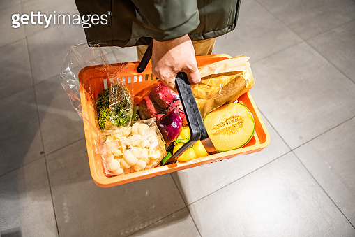 view of man holding grocery basket do shopping