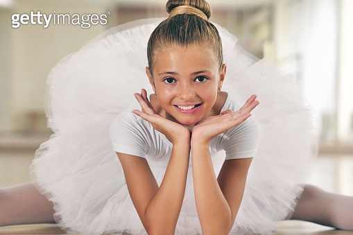 Portrait of a beautiful very young girl, in a dance school wearing a white tutu, she trains alone to learn new dance steps.