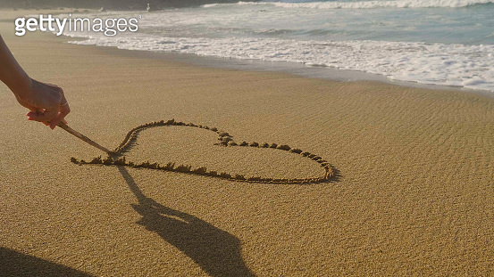 Beautiful painted heart on brown sand, sunset, sea background.