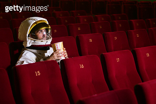 A movie astronaut looks at a movie while eating pop corn and enjoying the movie.