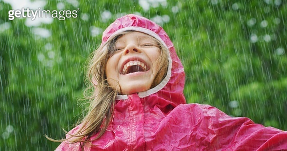 A happy girl is playing in the rain and is happy because she has fun. He opens his arms as a sign of freedom and love for nature.