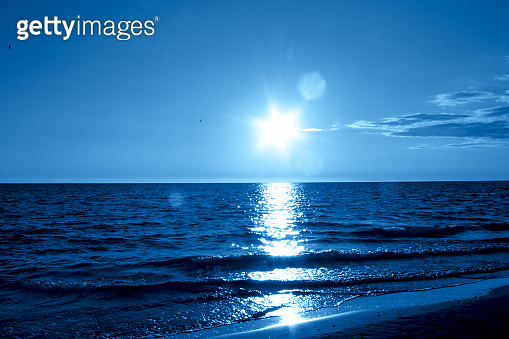 Seascape with the sunset in the trendy classic blue color of the year.