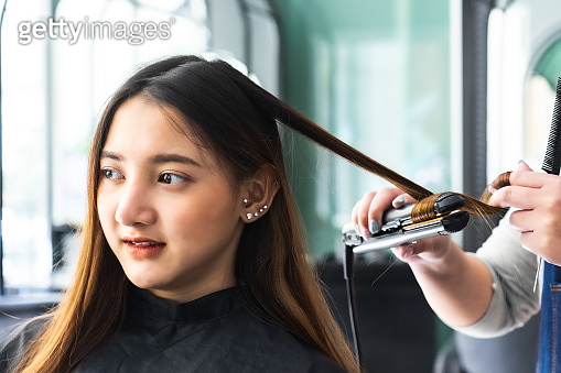Young Asian beautiful woman having her hair cut at the hairdresser's..Scissors cut the girls hair.Barber student cutting hair using puppet