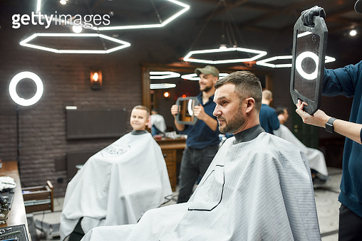 Look here. Two barbers holding mirrors and showing haircuts to father and son sitting in armchair at modern barbershop. Family visiting barber shop