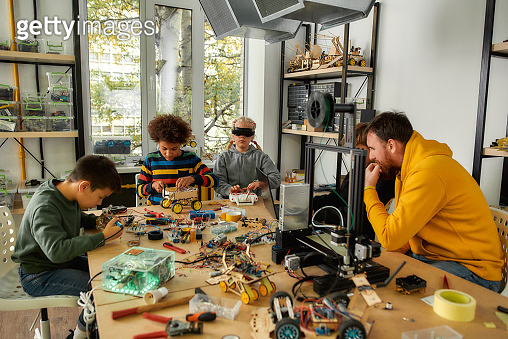 Learning, friendship and fun. Young technicians building robots and vehicles, using soldering iron to join chips and wires, testing toys together with a male teacher at a stem robotics class