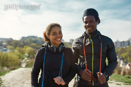 Beautiful young african couple in sportswear holding jumping ropes, looking at camera and smiling while working out together outdoors