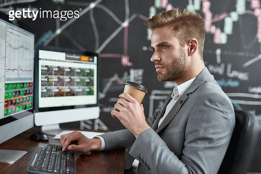 Get your financial power. Portrait of successful trader looking aside and drinking coffee while sitting in front of multiple monitors in the office. Blackboard full of data analyses in background.