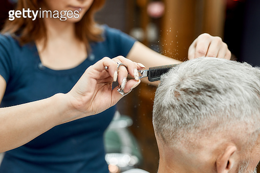 Getting hairstyle. Close up portrait of young barber girl with scissors and comb in hands doing haircut for her mature client. Man visiting beauty salon