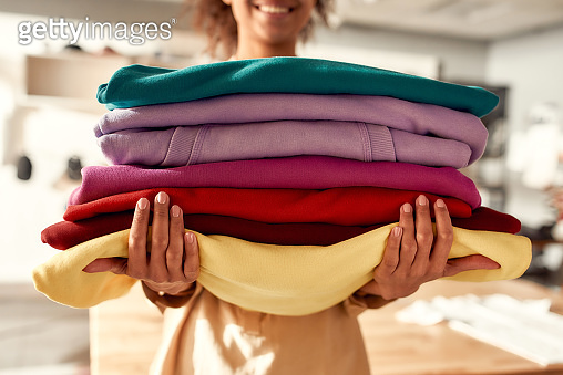 From design to delivery. Cropped shot of woman holding stack of colorful sweatshirts, hoodies while standing in the store. Clothes at custom T-shirt, clothing printing company