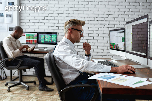 Becoming financially strong. Middle-aged trader sitting by desk in front of computer monitor while working in the office. His colleague in the background