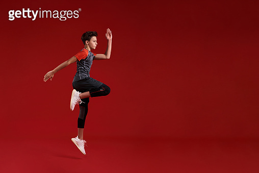 Cardio training. A teenage boy is engaged in sport, he is looking aside while jumping. Isolated on red background. Fitness, training, active lifestyle concept. Horizontal shot