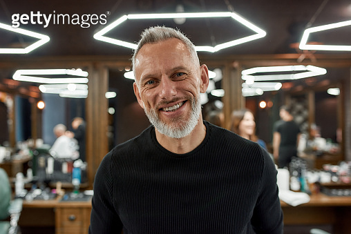 Happy handsome middle-aged man in barbershop. Portrait of elegant bearded man looking at camera and smiling while visiting barber shop or salon