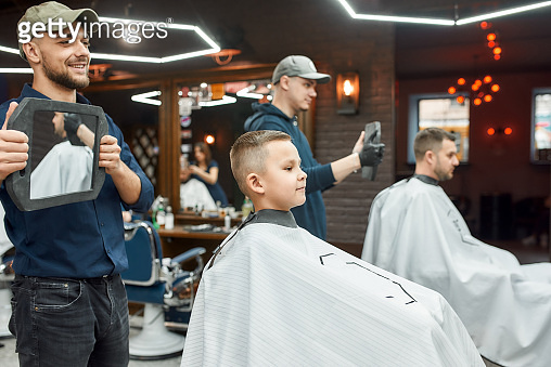 Haircut for little boy. Young smiling barber holding a mirror and showing the result of his work to cute little boy sitting in barber shop chair. Child visiting barber shop