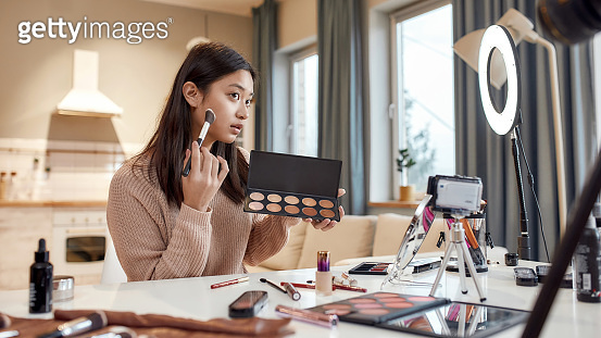 Bring Perfect Beauty. Young female blogger applying makeup, testing cosmetic products while recording a tutorial video for her beauty blog using camera at home