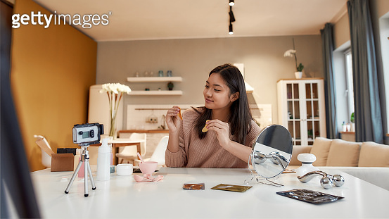 Put yourself First. Young female blogger recording a tutorial video for her beauty blog about skincare routine. Vlogger testing eye patch, recording video for social network