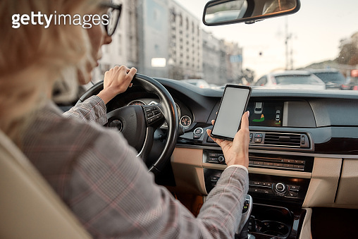 Important e-mail. Back view of beautiful business woman using her smartphone while driving a car