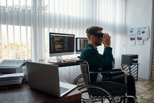 Young male web developer in a wheelchair wearing virtual reality glasses while working at his workplace in modern office. Multiple computer screens with program code