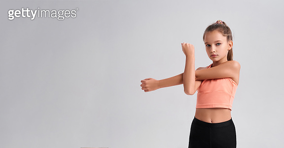 Get fit to be awesome. Flexible cute little girl child looking at camera while doing exercise isolated on a white background. Sport, training, fitness, active lifestyle concept. Horizontal shot