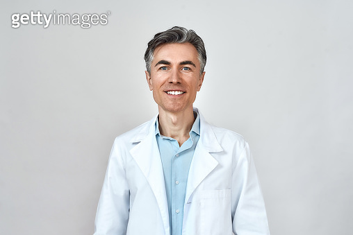 Portrait of happy senior caucasian doctor in medical uniform looking at camera and smiling while standing against grey background, posing in studio