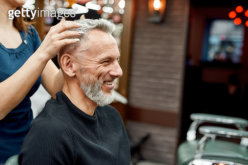 I like it. Happy mature bearded man smiling while female barber making haircut for him, he is sitting in barbershop