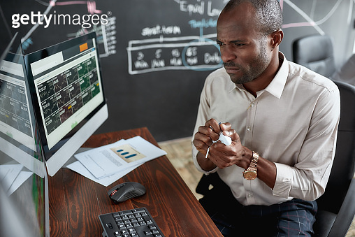Money is required. Stylish african businessman, trader sitting by desk in front of multiple monitors. He is getting angry while crumpling papers.