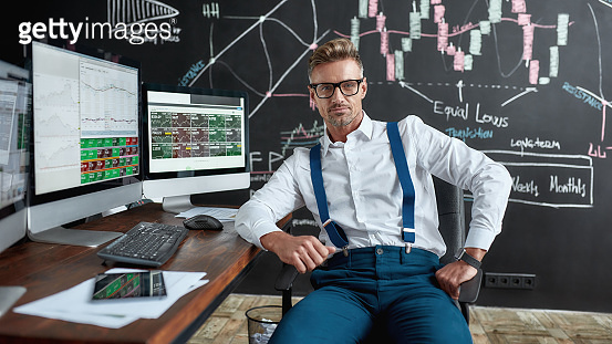 Letting money grow. Middle-aged caucasian trader in glasses looking at camera while sitting by desk in front of computer monitor. Blackboard full of charts and data analyses in background.