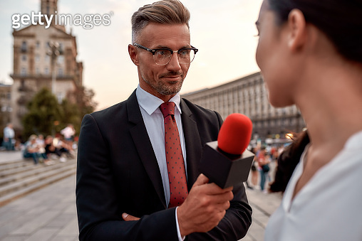 First. Best. Live. Professional reporter interviewing woman on urban street. Journalism industry, live streaming concept