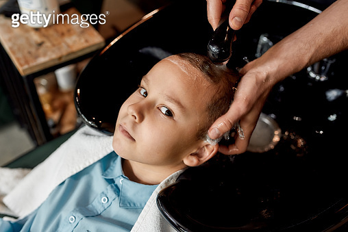 Hairwash. Cute little boy leaning on the sink in barbershop and looking at camera while male barber washing his hair