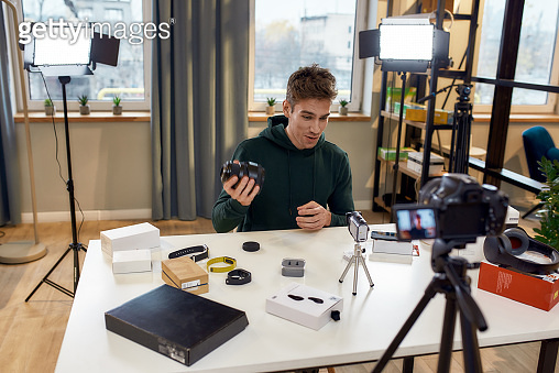 Create it. Young male technology blogger recording video blog or vlog about new camera lens and other gadgets at home studio. Blogging, Work from Home concept