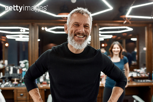Perfect beard. Portrait of elegant and happy bearded man looking at camera and smiling while visiting barber shop or salon