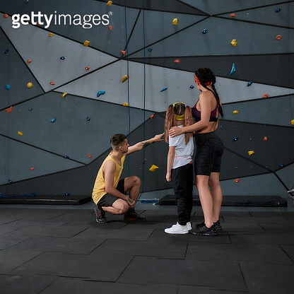 Full length shot of active little girl going to climb, male and female instructor helping kid, standing against artificial training climbing wall