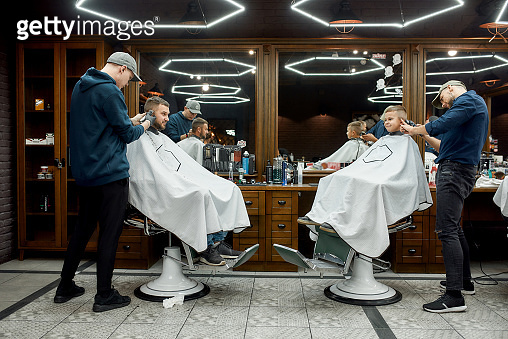 Family at barbershop. Young father and his little happy son sitting together in chairs in the modern barbershop while two barbers making haircuts for them