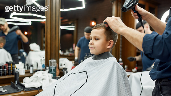 Kids hairstyle. Little cute boy sitting in armchair at barbershop while barber drying his hair. Getting haircut